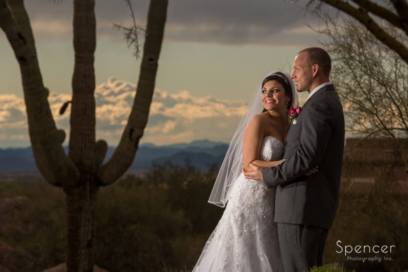bride and groom pose in desert for picture during destination wedding
