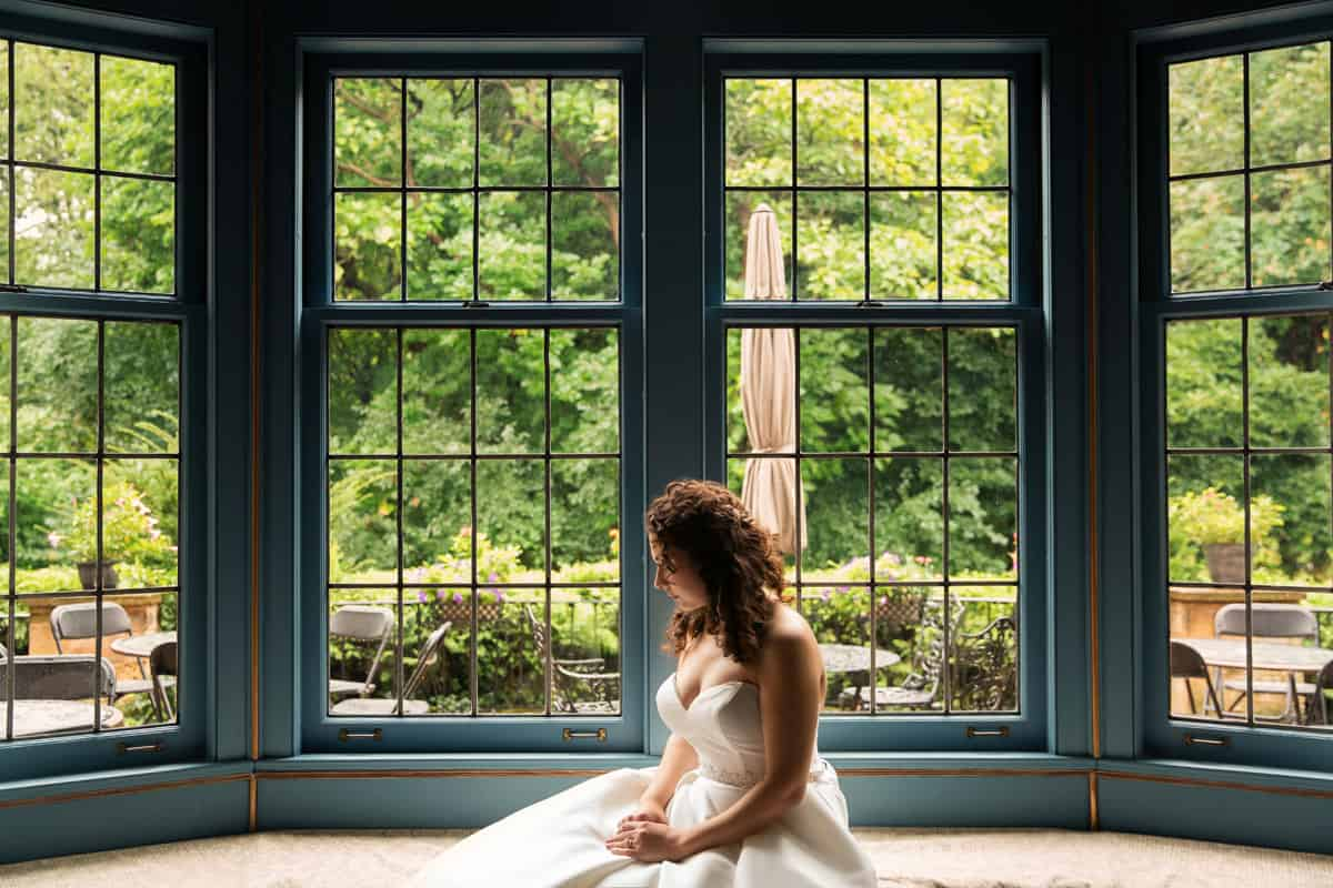 bride sitting in O'Neil House on her wedding day