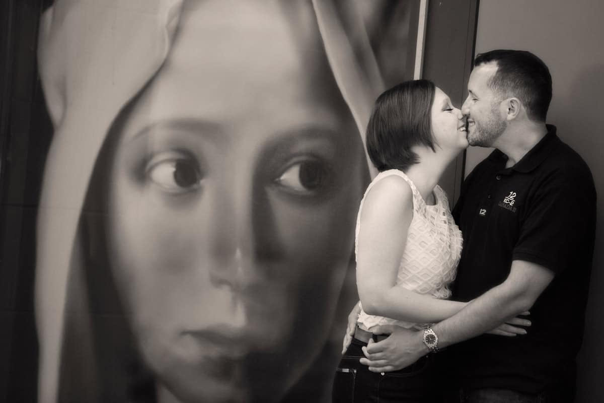 cleveland engagement picture of couple kissing next to artwork