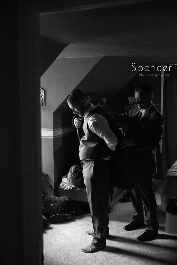 dad helping groom putting on jacket