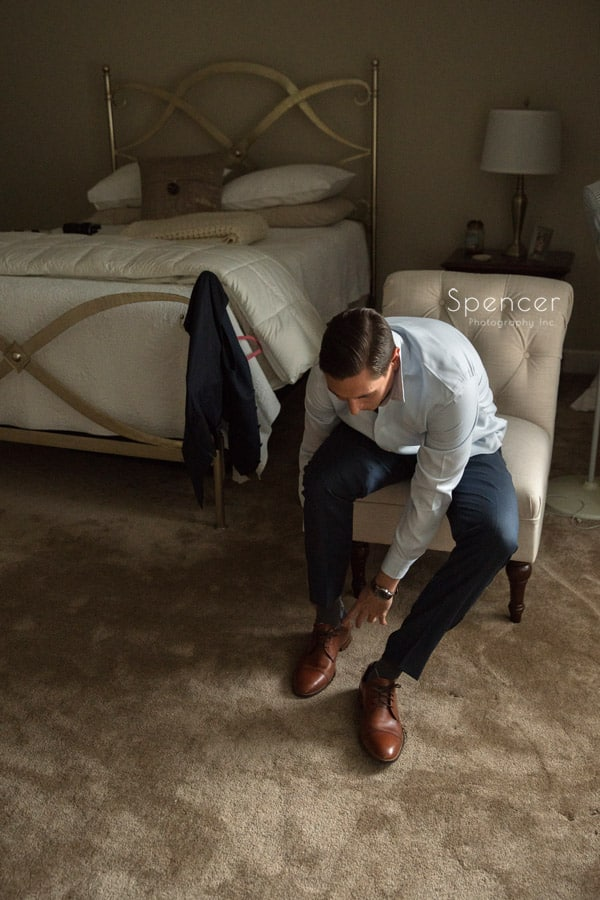 groom putting on wedding day shoes in cleveland home