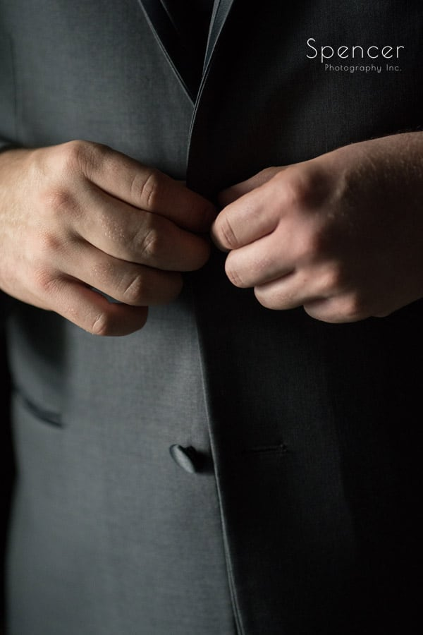 groom buttoning his tux jacket