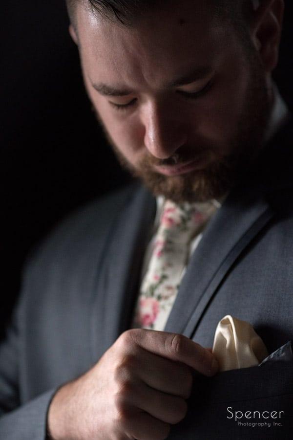 groom adjusting pocket square