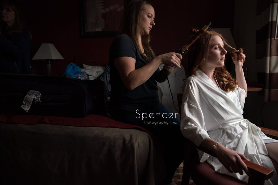 bride getting hair done on wedding day