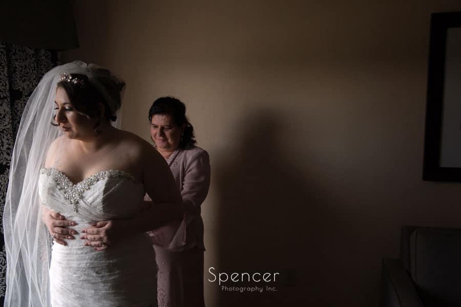 mom helping bride into wedding dress