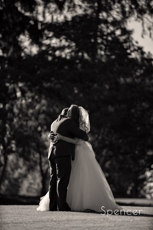 bride and groom hug on golf course at Portage Country Club