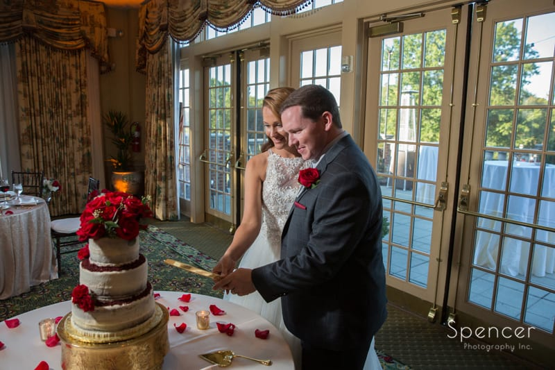 bride and groom cutting wedding cake at portage country club