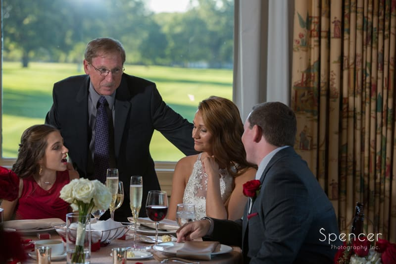 dad speaking with bride and groom at portage country club reception