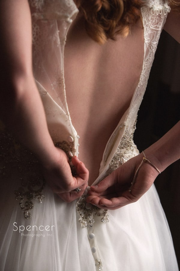 bride buttoning her wedding dress