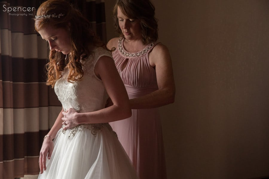 mother of bride helping bride into wedding dress