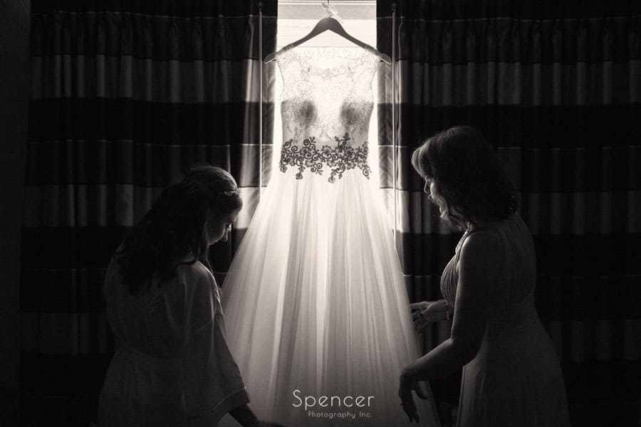 bride and mom handling wedding dress