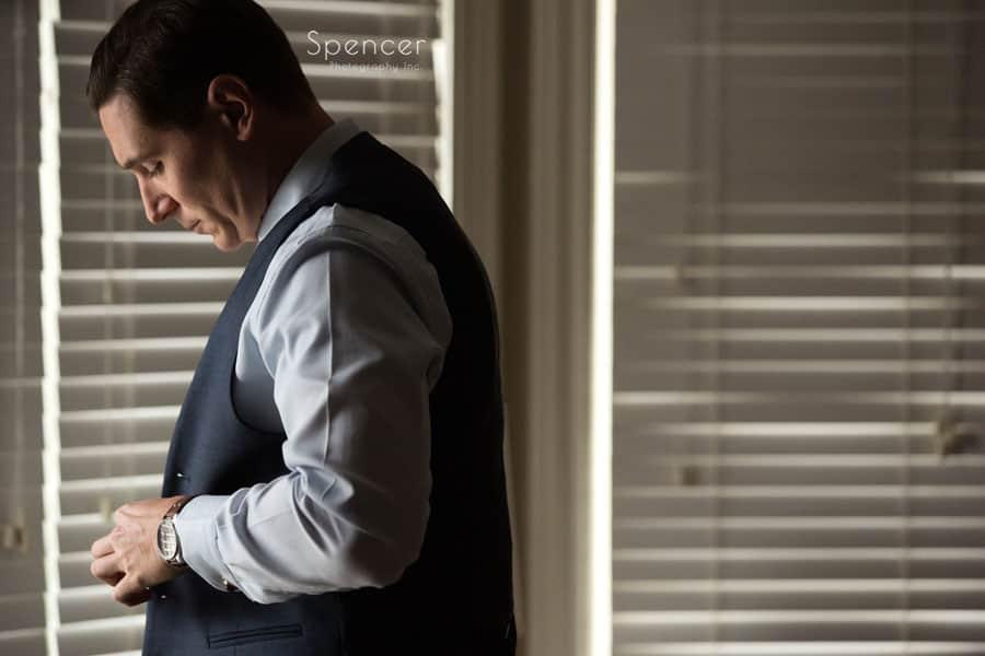 groom buttoning vest before cleveland wedding