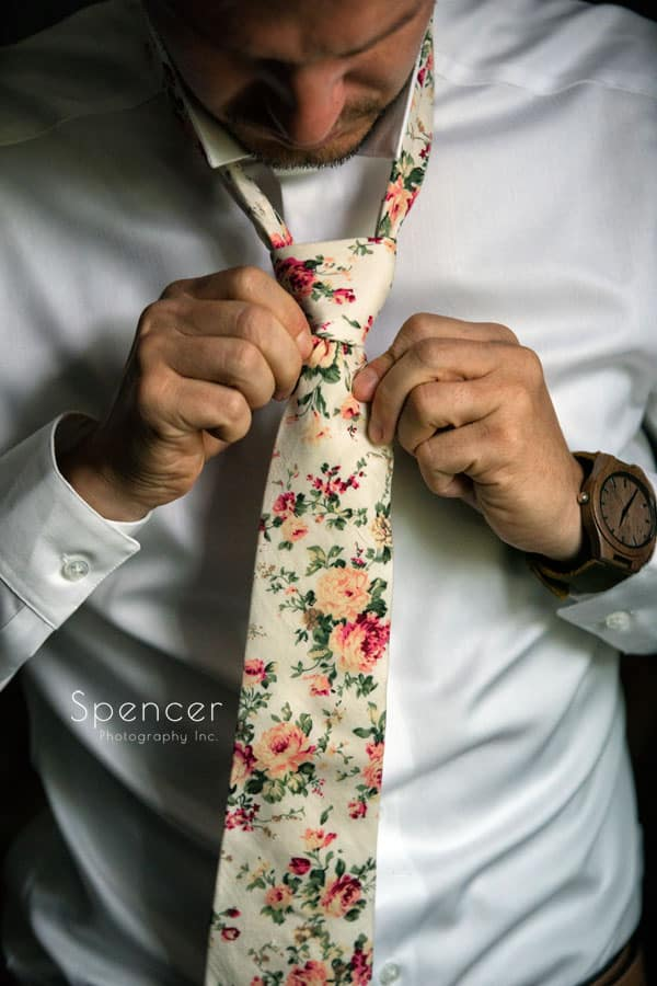 groom tying his wedding day tie