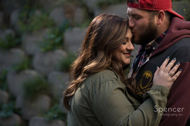 man kisses woman in fall engagement picture at brandywine falls