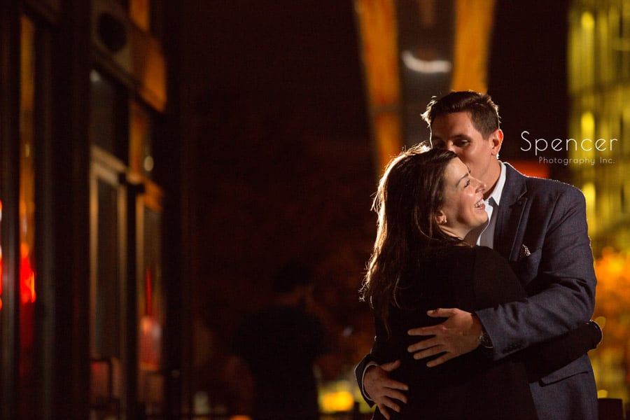 man kisses woman on east fourth cleveland during evening engagement pictures