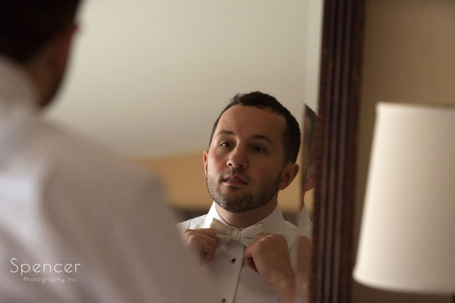 groom straighten tie in locker room at Firestone