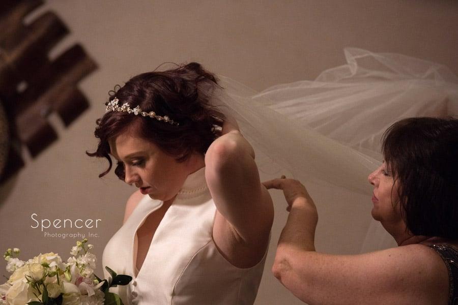 mom adjusting brides wedding veil in locker room at firestone