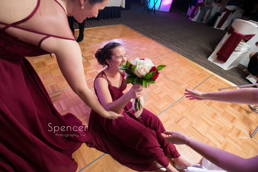 bridesmaid sitting of floor after catching bridal bouquet