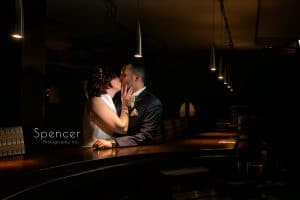 bride and groom kissing in bar at firestone country club