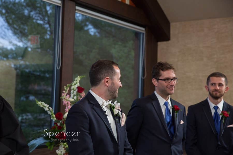 groom reacting to bride walking down aisle
