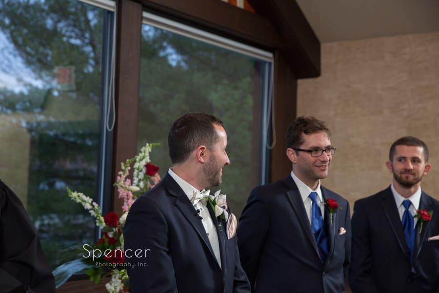 groom reacting to bride walking down aisle