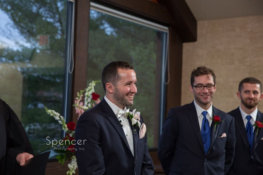 groom smiling at bride walking down aisle at lodge at firestone