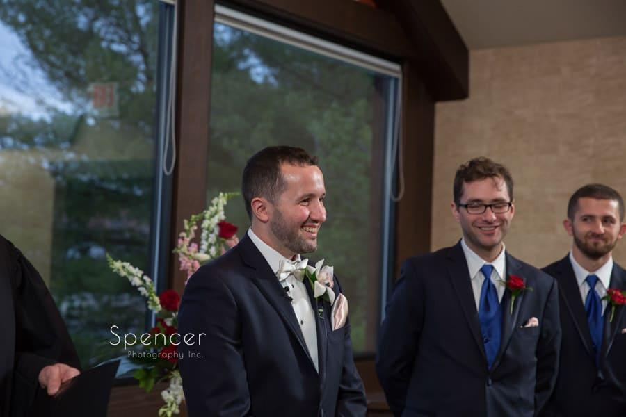 groom smiling at bride walking down aisle at lodge at firestone