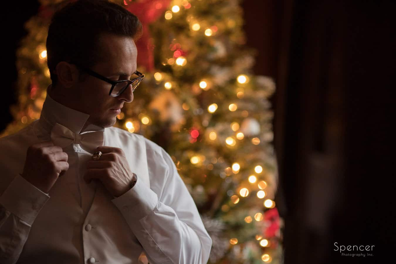groom adjusting bowtie in front of christmas tree