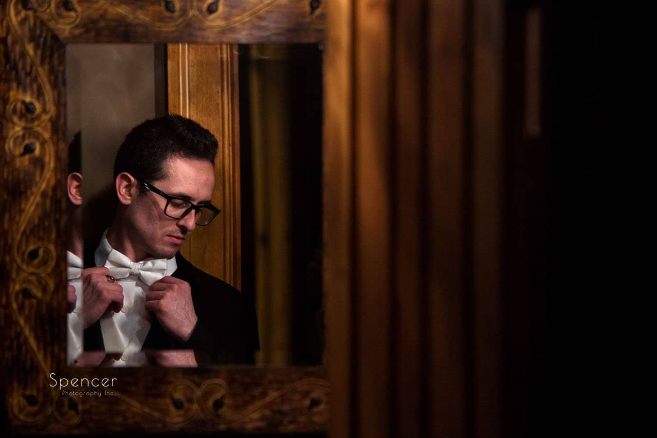 picture of groom in mirror on his christmastime wedding day