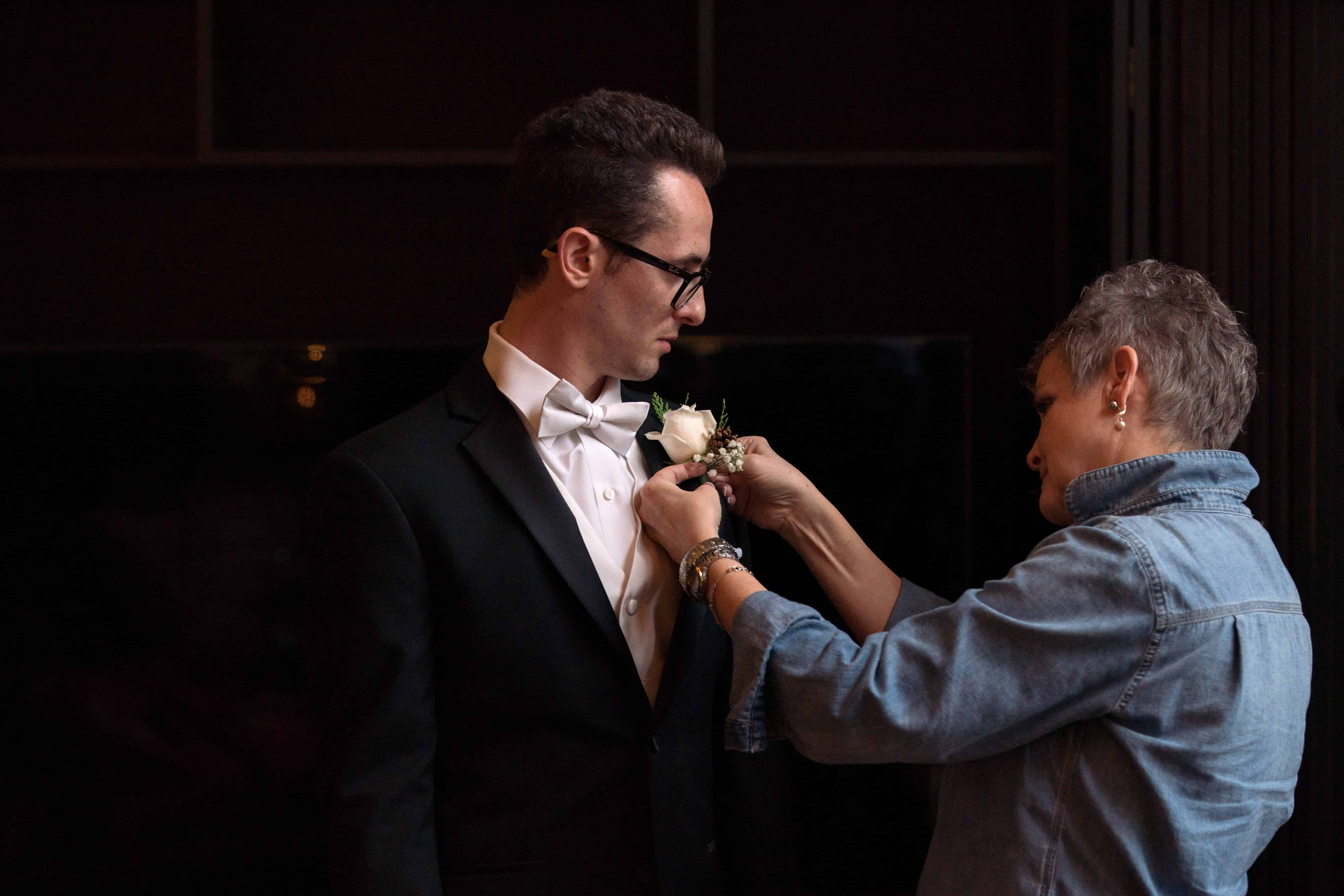 grooms mom putting on his wedding day flower