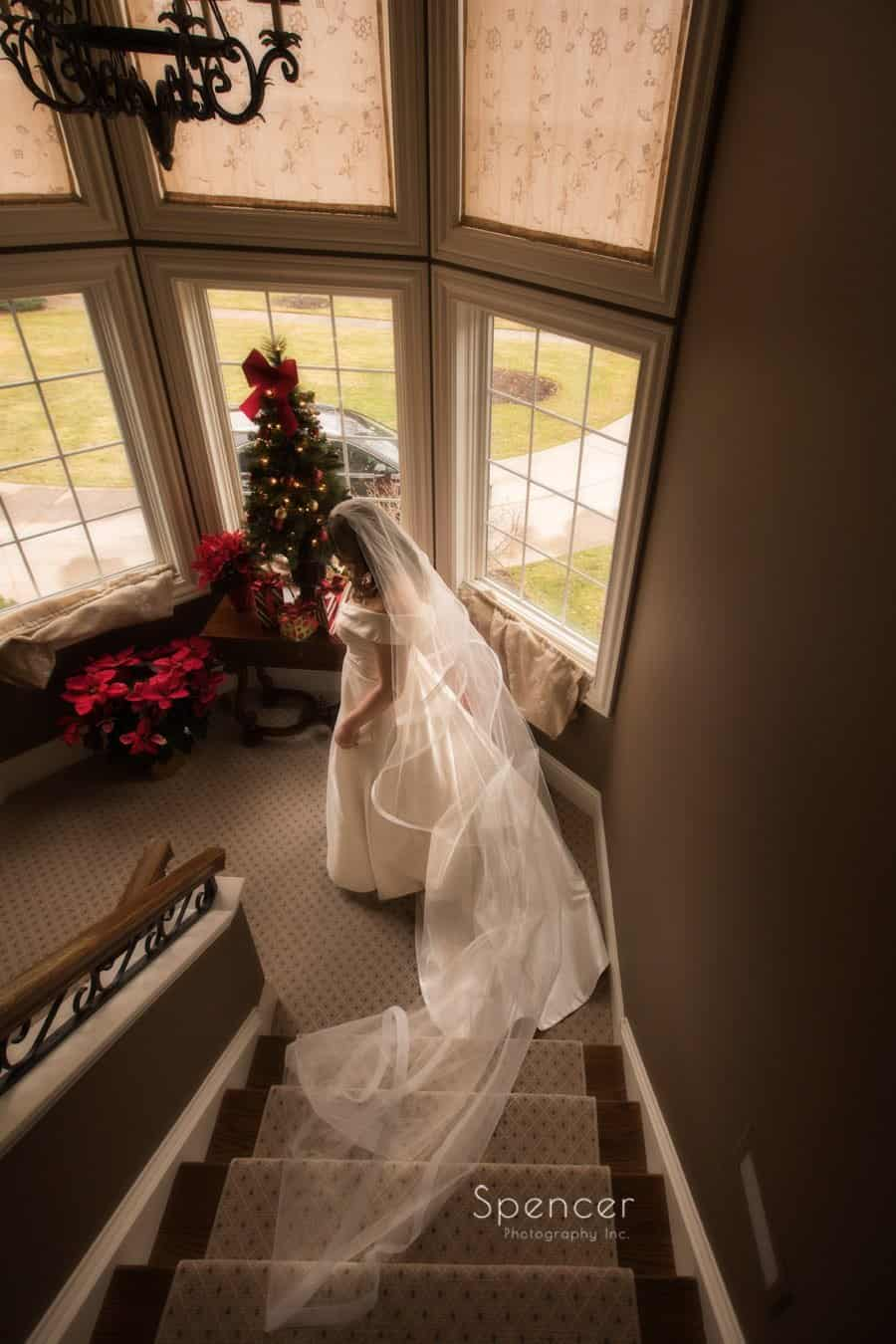 bride walking down staircase on wedding day