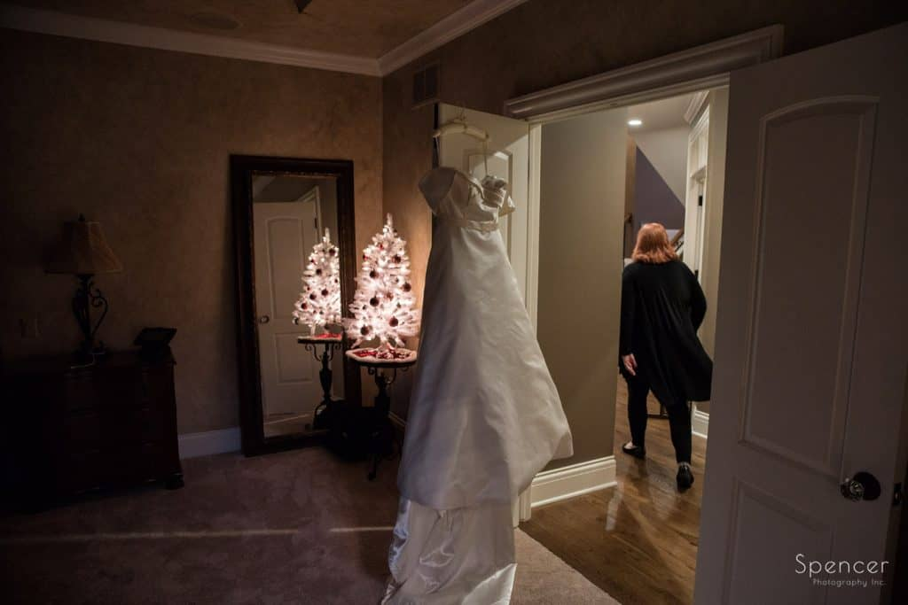 wedding dress haning with christmas tree in background