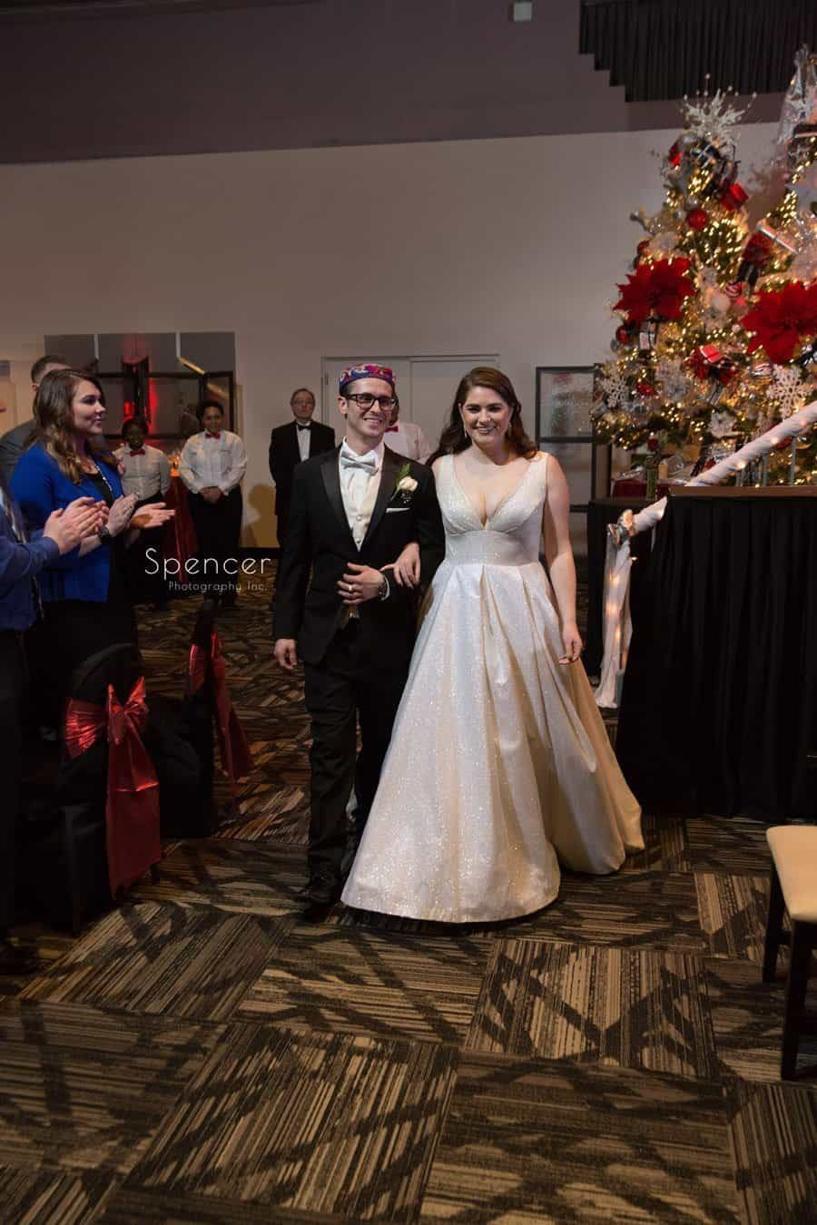 bride and broom enter their christmas wedding reception at landerhaven