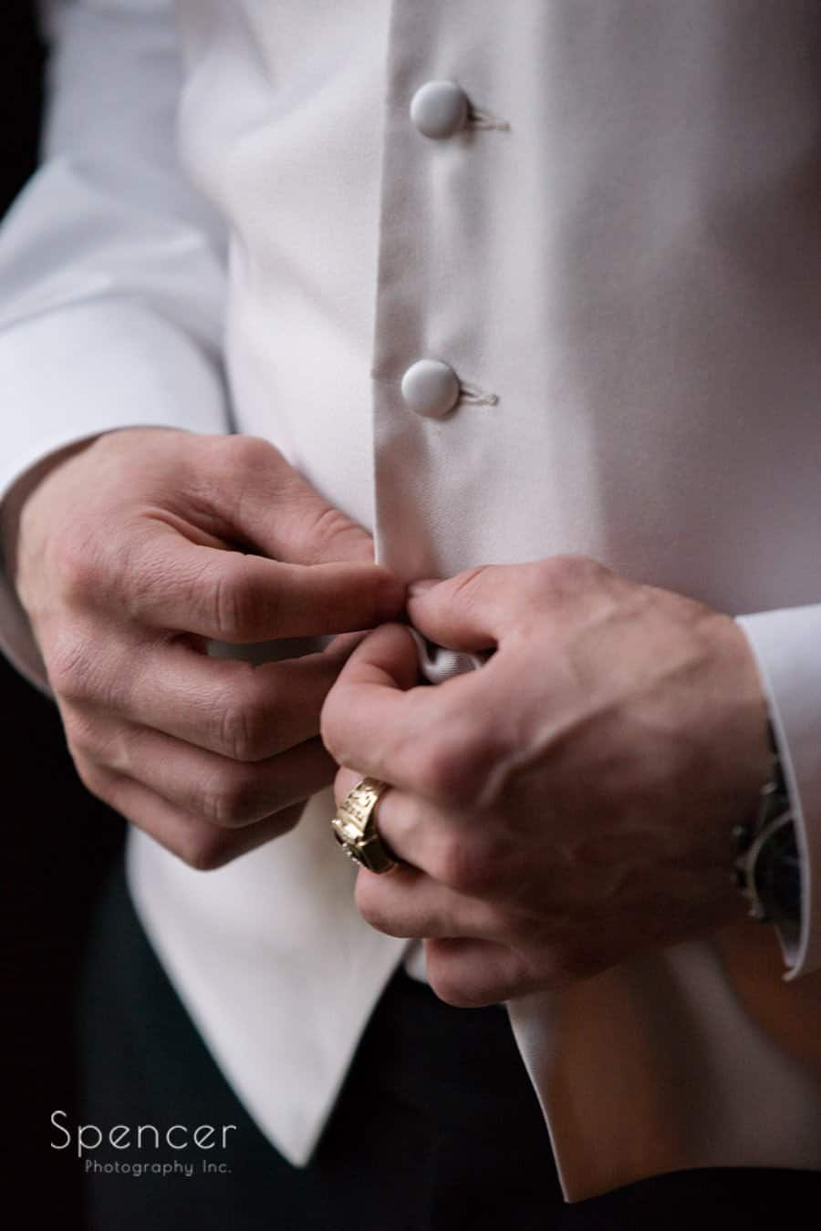 groom buttoning his wedding day tux