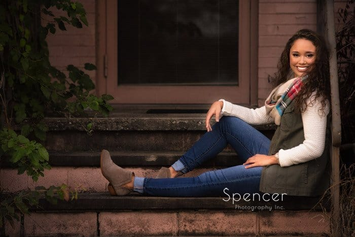 high school senior sits on stoop for senior photo