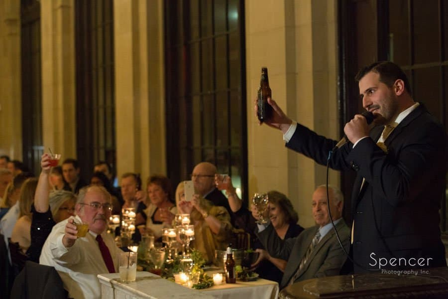 best man toasts his beer at ariel wedding reception