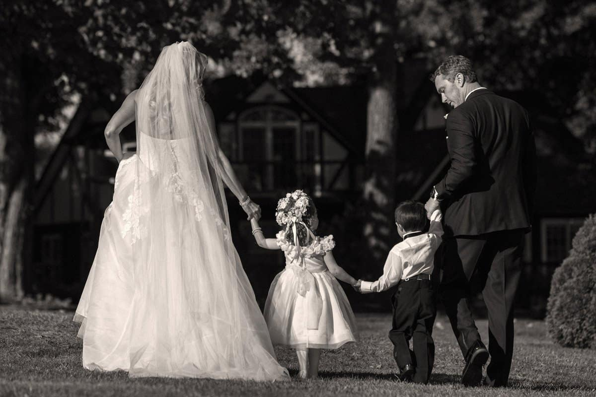 bride and groom walking children at their wedding