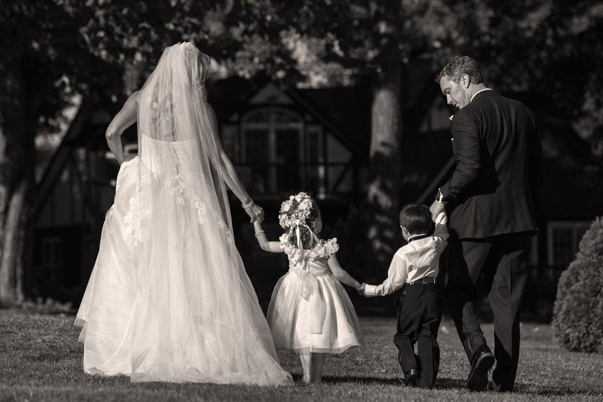 bride and groom walking children at their wedding