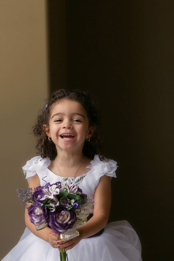 flower girl laughing holding bouquet before wedding in cleveland