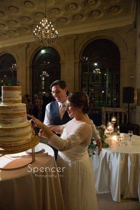 groom helping bride cut cake at ariel pearl reception