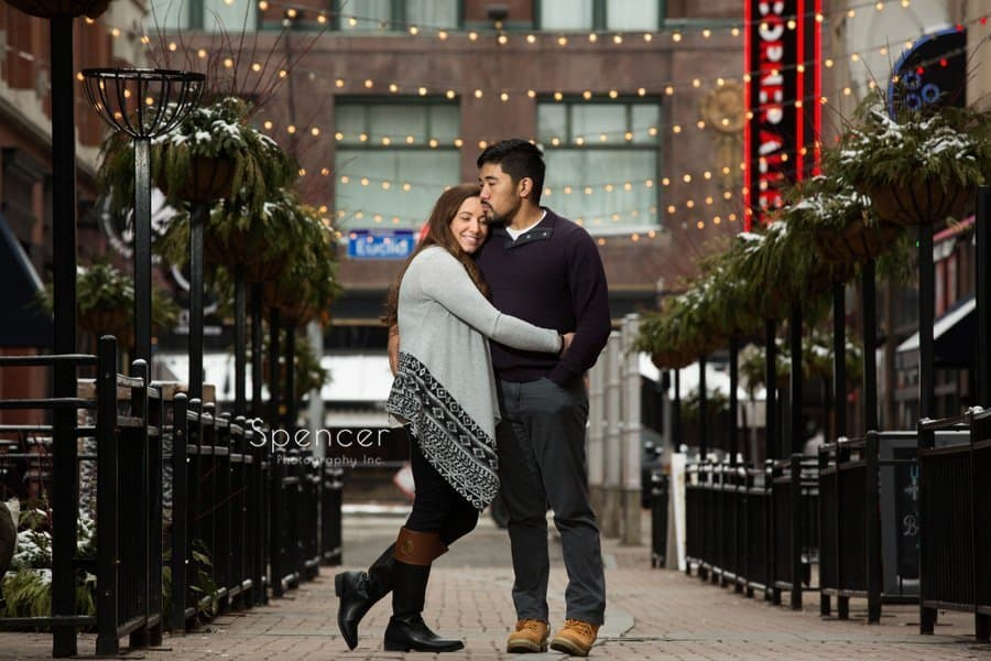 man kissing woman in engagement picture on Cleveland East Fourth Street