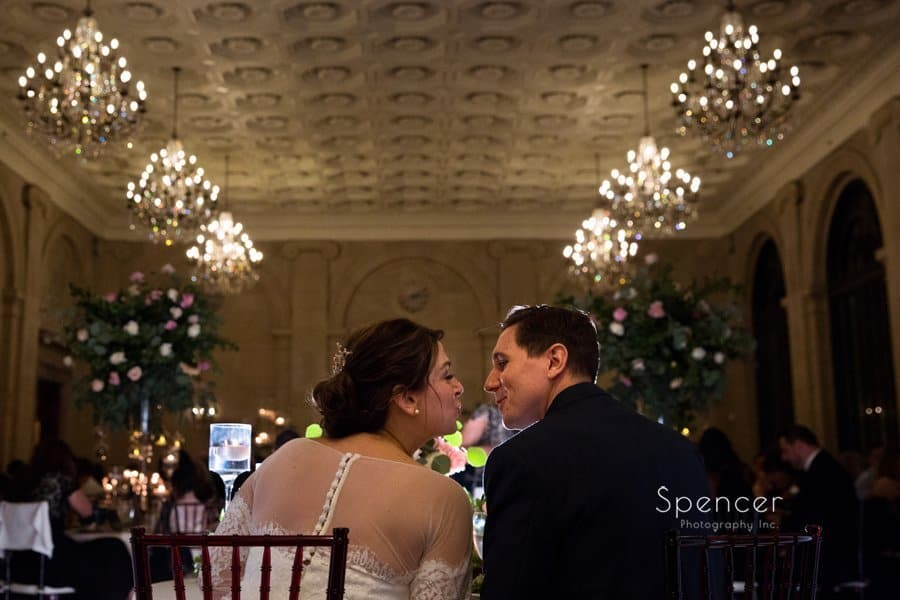 wide angle picture of bride and groom kissing at ariel pearl wedding reception
