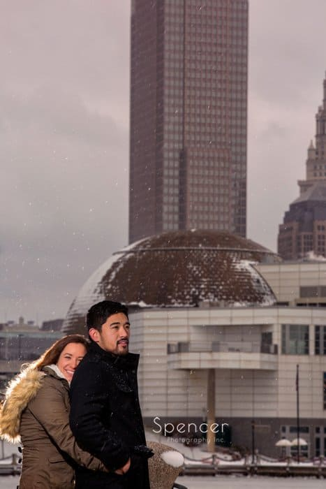 winter engagement picture of woman hugging man in front of downtown Cleveland