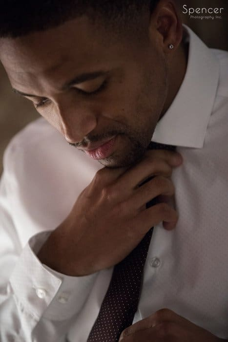 close up picture of groom adjusting tie before his cleveland wedding