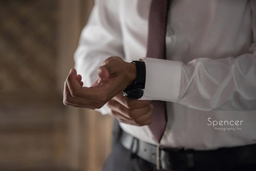 groom adjusting tux sleeve before his wedding in Middleburg Heights