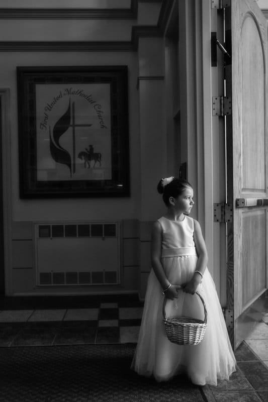 flower girl standing inside church waiting for wedding to start