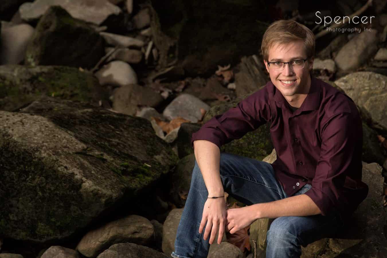 high school senior sitting in rocks in cleveland park