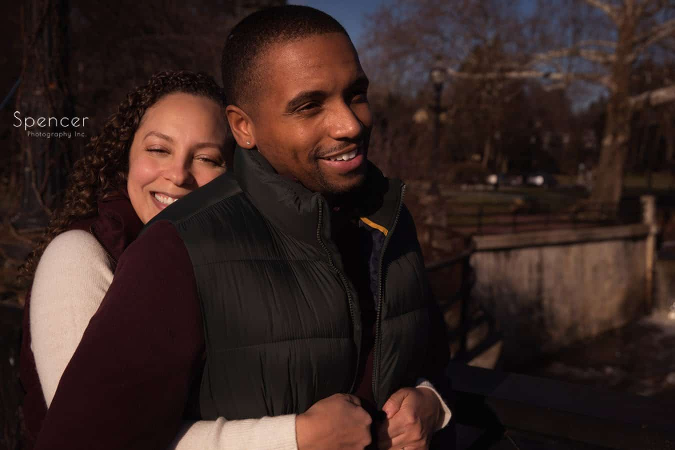 woman hugs man in engagement pictures in Chagrin Falls