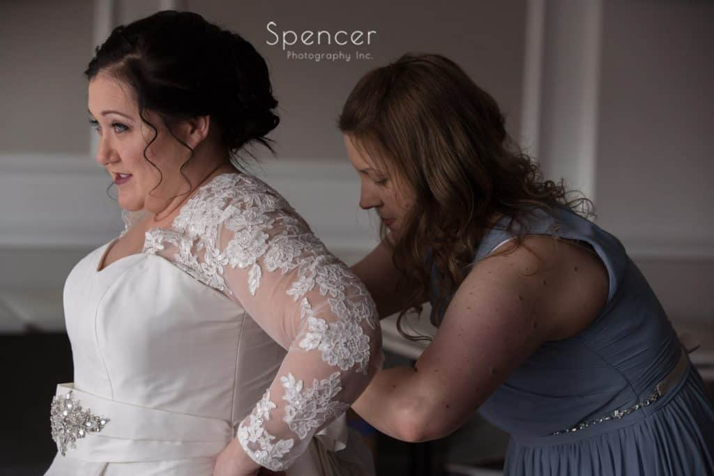 bride getting help from bridesmaid at Vosh Lakewood
