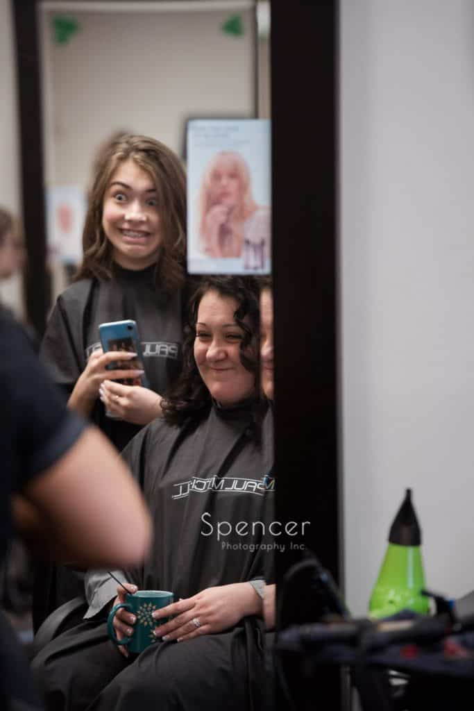 bride laughing with daughter in hair salon